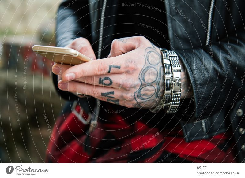 Tattooed man hands with smartphone Telecommunications Telephone PDA Technology Internet Man Adults Hand Fingers Street Jacket Leather Love Modern Black mobile