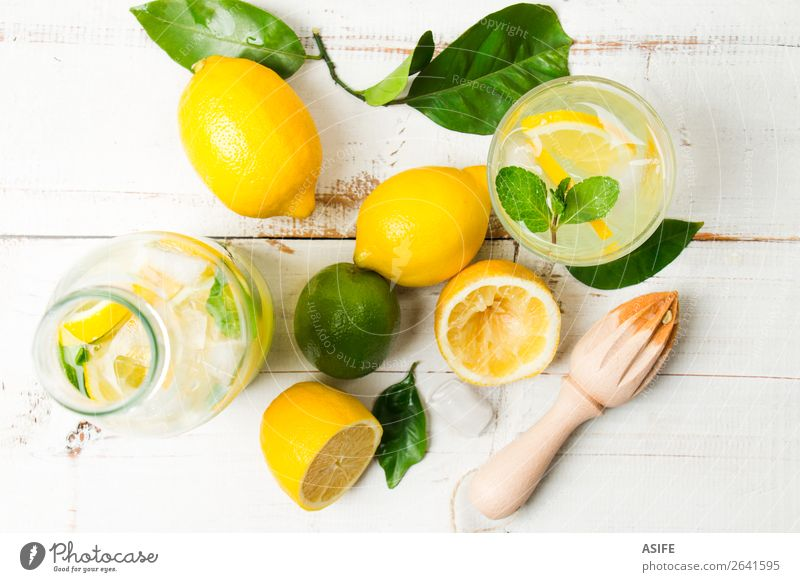 Homemade lemonade with reamer on white wooden table Fruit Diet Beverage Lemonade Juice Summer Table Leaf Wood Cool (slang) Fresh Above Yellow Green White lime