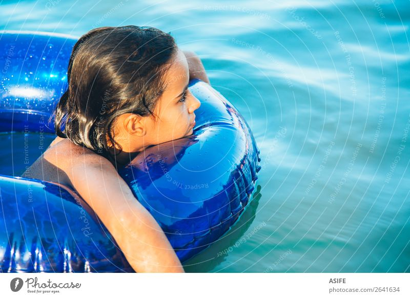 Happy little girl floating with a ring in the water Lifestyle Joy Beautiful Relaxation Swimming pool Leisure and hobbies Playing Vacation & Travel Summer Beach