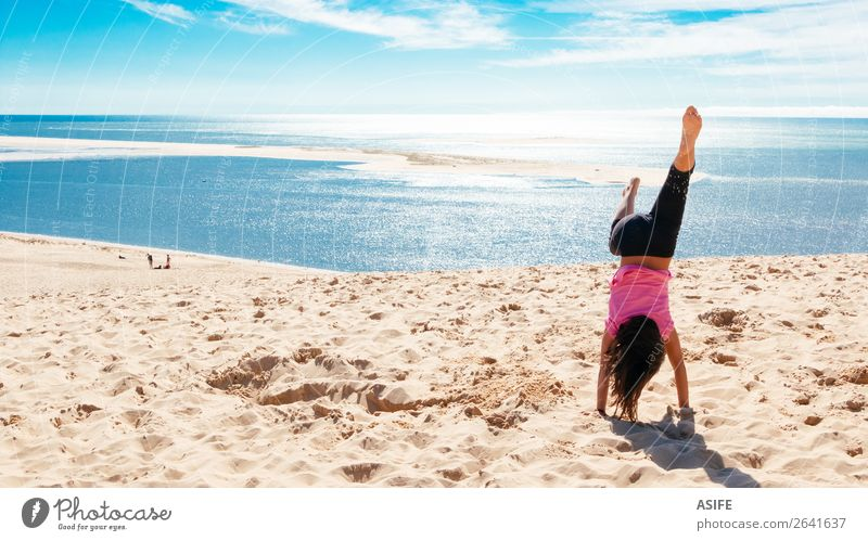 Happy little girl doing a handstand on the beach Joy Beautiful Leisure and hobbies Playing Vacation & Travel Tourism Summer Beach Ocean Child Woman Adults