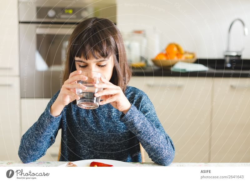 Cute thirsty girl drinking water in a glass at home Nutrition Eating Lunch Dinner Drinking Joy Happy Beautiful Table Kitchen Child Sit Appetite Thirsty kid