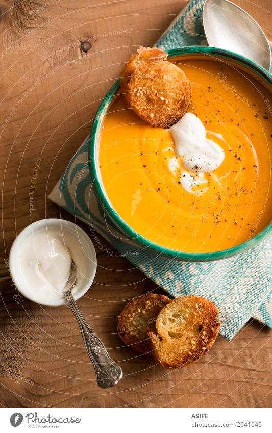 Pumpkin soup with coconut cream and spices Cheese Vegetable Bread Herbs and spices Vegetarian diet Diet Bowl Winter Autumn Wood Orange butternut squash soup