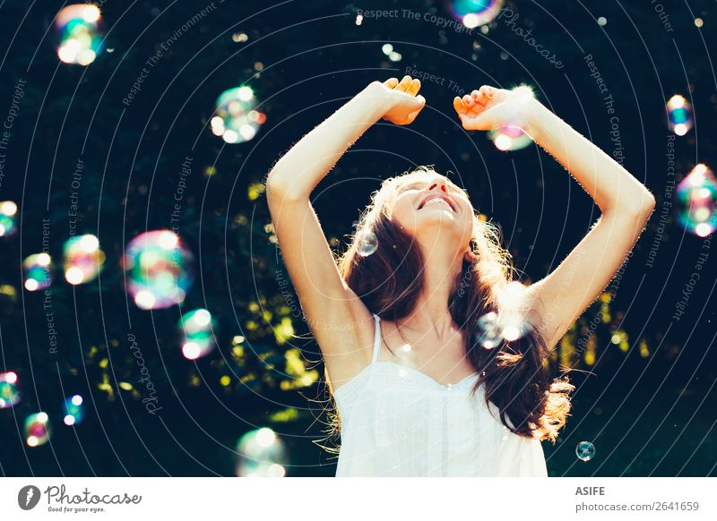 Girl having fun with bubbles Joy Happy Beautiful Playing Summer Feasts & Celebrations Human being Woman Adults Nature Warmth Park Dream Happiness Soft Green