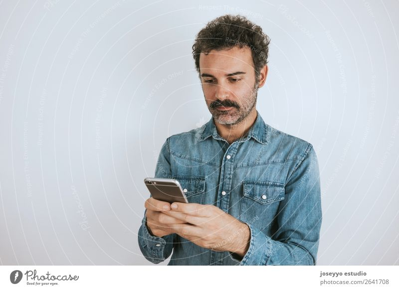 Portrait of a man with mustache using his smartphone. Lifestyle Face Cellphone PDA Human being Adults Fashion Shirt Stand Cool (slang) Hip & trendy