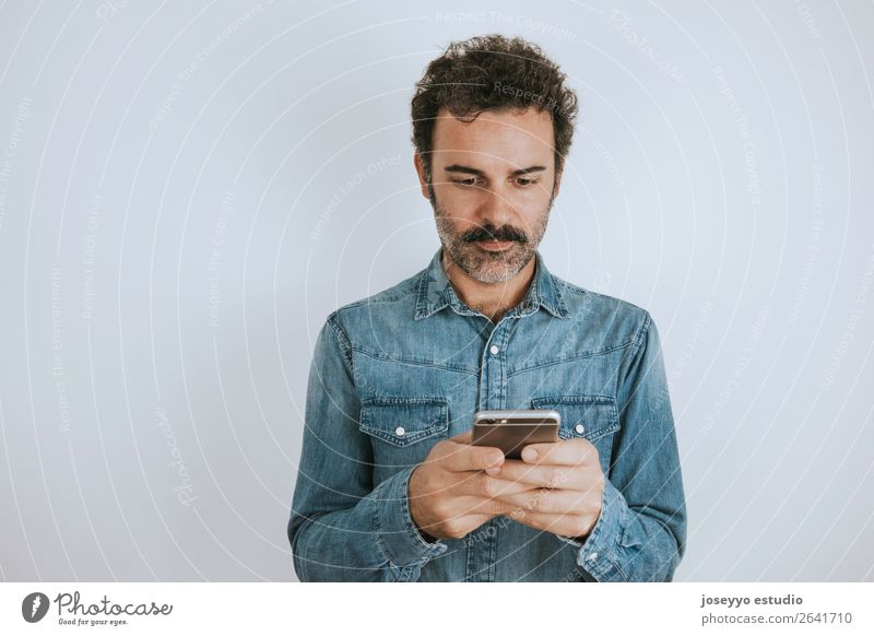 Portrait a man with mustache using his smartphone. Lifestyle Face Cellphone PDA Human being Adults Fashion Shirt Stand Cool (slang) Hip & trendy Self-confident