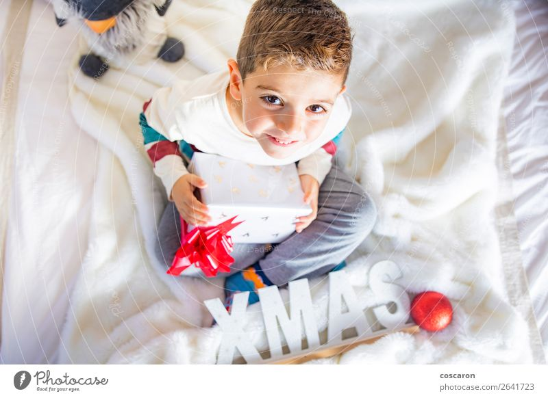 Littlr kid on Christmas day on the bed with a gift Child Human being Christmas & Advent White Red Tree House (Residential Structure) Relaxation Joy Winter Face