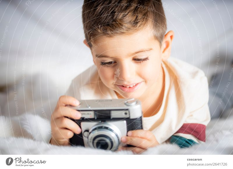 Beautiful boy with a photographing camera in the bed Lifestyle Joy Happy Face Vacation & Travel Child Camera Technology Human being Baby Toddler Boy (child)