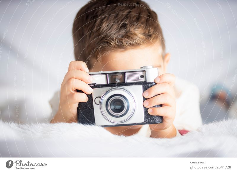 Beautiful boy with a photographing camera in the bed Lifestyle Joy Happy Face Vacation & Travel Room Bedroom Child Camera Technology Human being Baby Toddler