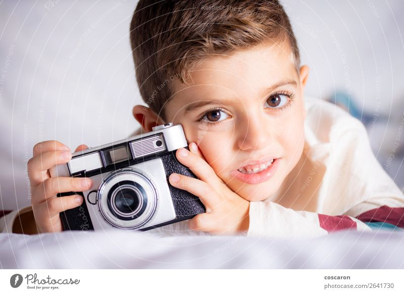Beautiful boy with a photographing camera in the bed Lifestyle Joy Happy Face House (Residential Structure) Room Bedroom Education Child Apprentice