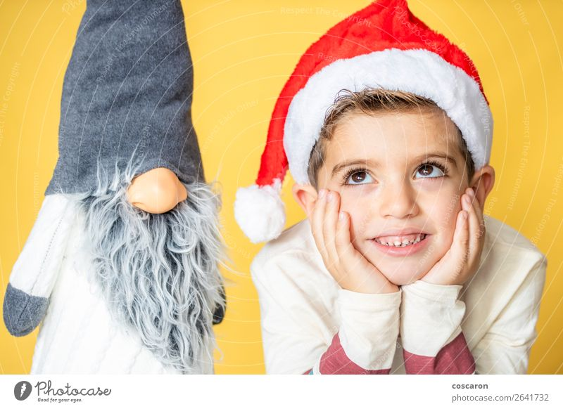 Child and a gnome with a yellow background on Christmas day Human being Christmas & Advent Beautiful White Red Joy Winter Face Lifestyle Love Funny Emotions