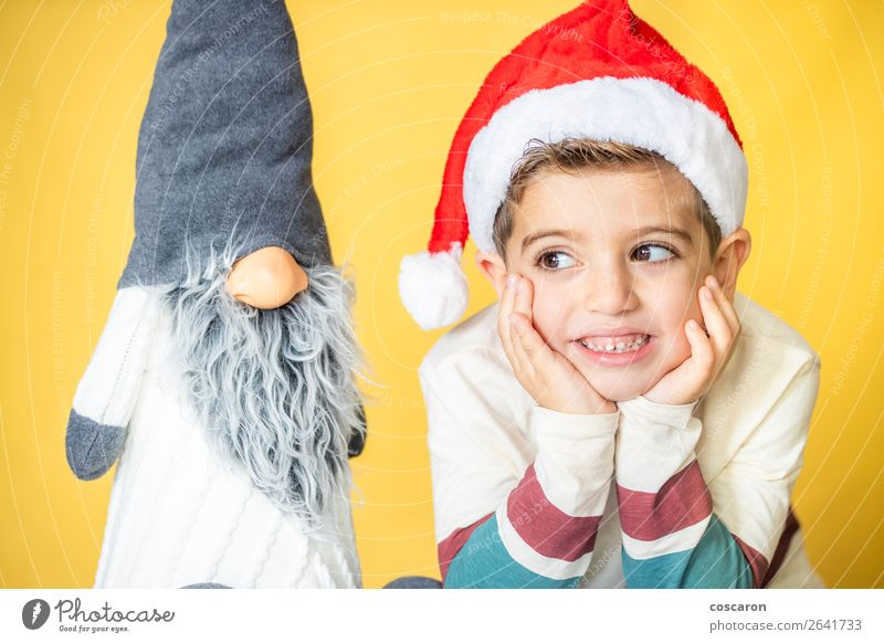 Child and a gnome with a yellow background on Christmas day Human being Christmas & Advent Beautiful White Red Joy Winter Face Yellow Love Funny