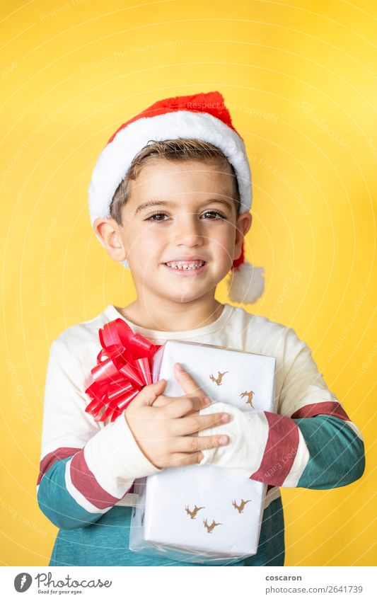 Little kid with a gift on a yellow background on Christmas Day Woman Child Human being Christmas & Advent Colour Beautiful White Red Joy Winter Lifestyle Adults