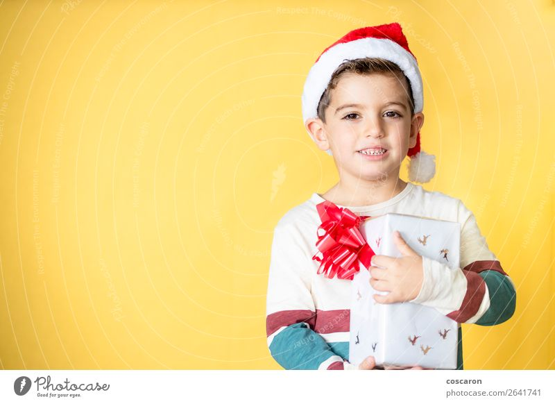 Little kid with a gift on a yellow background on Christmas Day Style Design Joy Happy Beautiful Winter Feasts & Celebrations Christmas & Advent New Year's Eve
