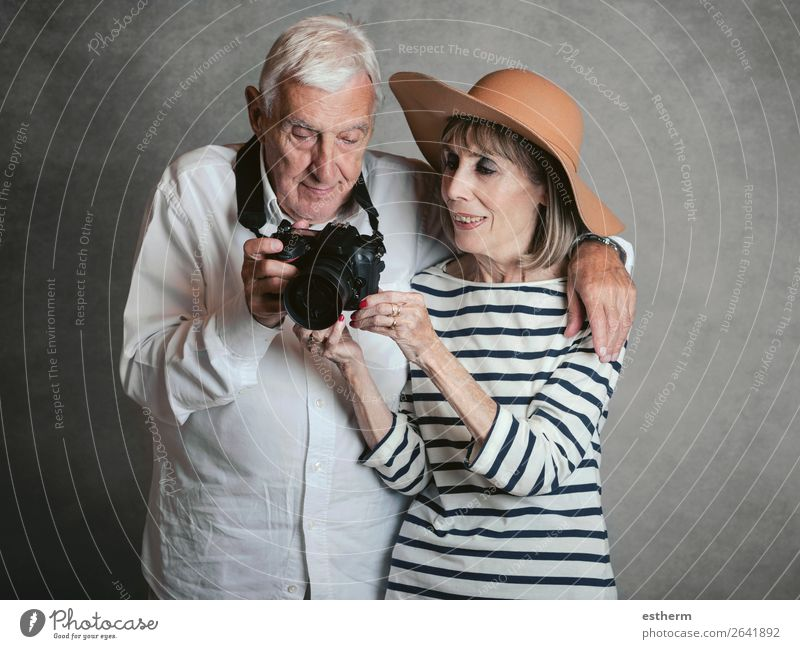 Portrait of happy senior couple with digital camera on gray background Lifestyle Joy Vacation & Travel Trip Cruise Retirement Camera Technology Human being
