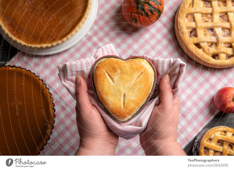Woman hands holding a heart shaped pie above a table Dessert Kitchen Adults Autumn Exceptional Many Tradition Thanksgiving day above view American apple pies