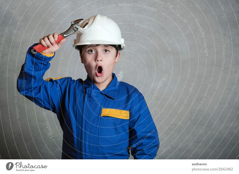 surprised child with a white helmet and holding a wrench Joy Child Work and employment Construction site Tool Hammer Human being Boy (child) Father Adults
