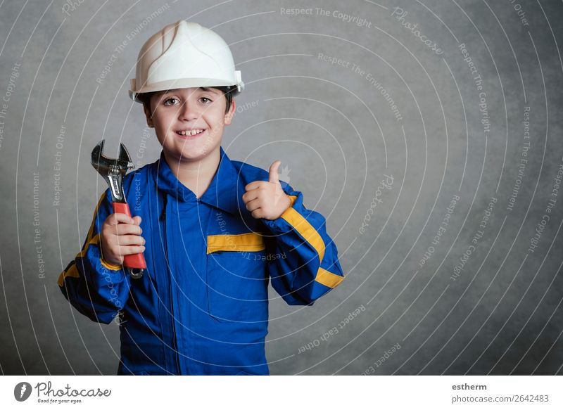 smiling child with a white helmet and holding a wrench Joy Child Work and employment Construction site Tool Hammer Human being Masculine Boy (child) Father