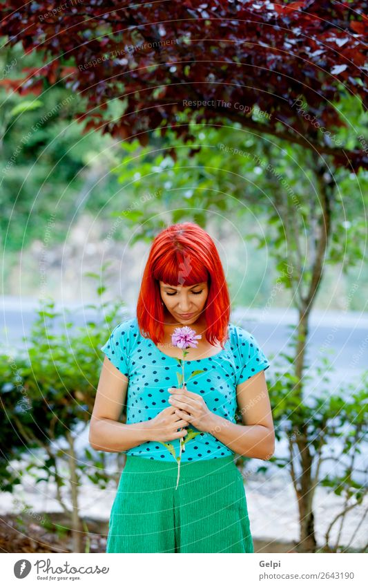 Redhead woman smelling a flower in a park Lifestyle Happy Beautiful Face Wellness Relaxation Fragrance Summer Garden Human being Woman Adults Nature Tree Flower