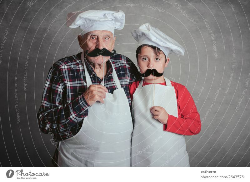 Grandfather With Grandson with cook hat and mustache on gray background Nutrition Diet Lifestyle Joy Leisure and hobbies Kitchen Restaurant
