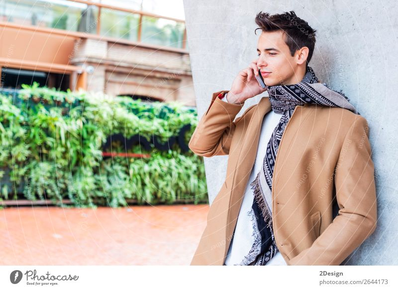 Modern young man with mobile phone in the street. Lifestyle Elegant Style Beautiful Hair and hairstyles Winter To talk Telephone PDA Man Adults
