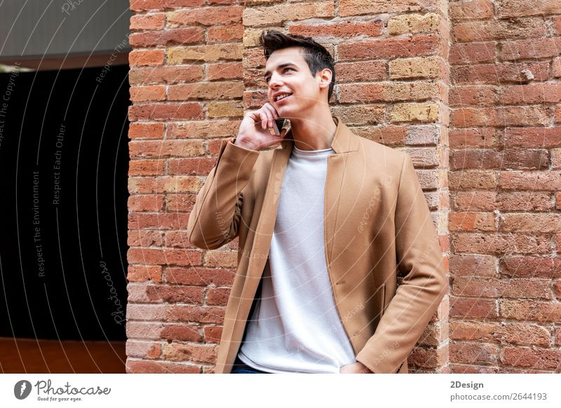 Portrait of modern young man with mobile phone in the street. Lifestyle Elegant Style Beautiful Hair and hairstyles Winter To talk Telephone PDA Man Adults