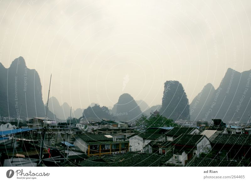 behind seven mountains. Landscape Sky Hill Rock Mountain karst landscape Yangshuo China Guilin Town House (Residential Structure) Roof Haze Fog Colour photo