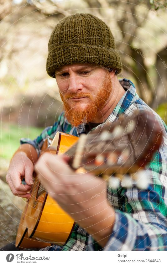 Hipster man with red beard playing a guitar Leisure and hobbies Playing Entertainment Music Human being Man Adults Musician Guitar Nature Red-haired Moustache