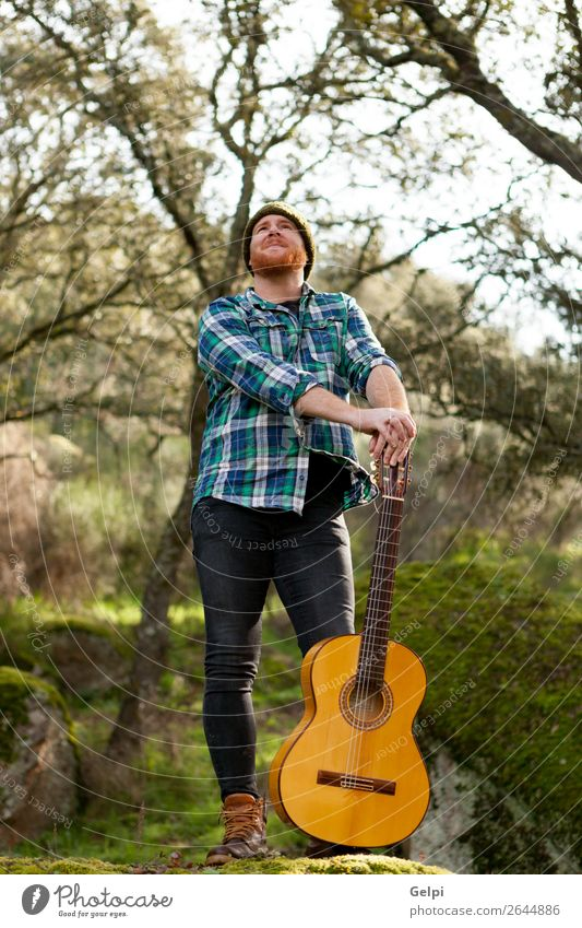 Hipster man with red beard and a guitar relaxs Leisure and hobbies Playing Entertainment Music Human being Man Adults Musician Guitar Nature Red-haired