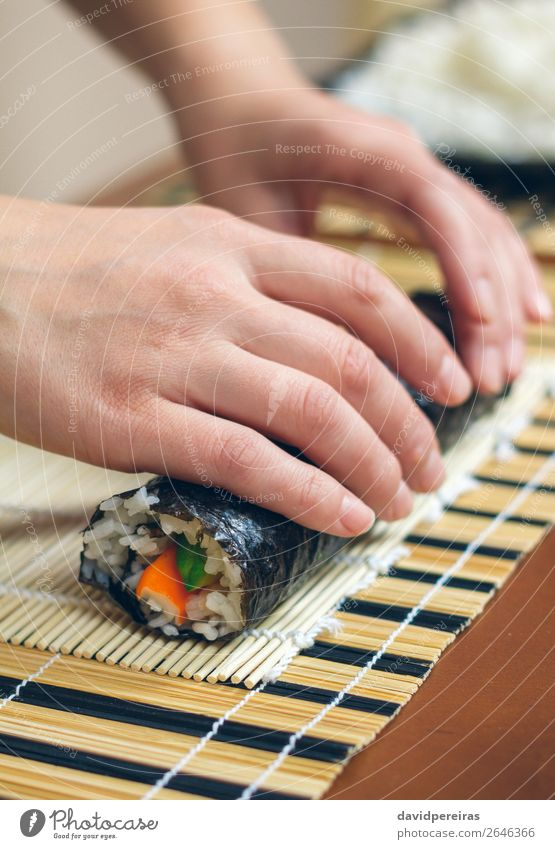 Woman chef hands rolling up japanese sushi Diet Sushi Human being Adults Hand Make Fresh preparing california roll crab stick avocado Rice food sheet girl
