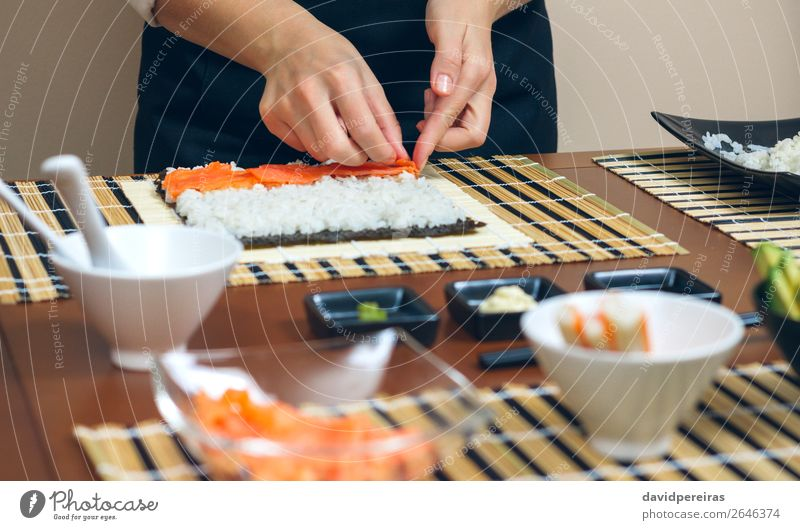 Chef hands placing ingredients on rice Seafood Diet Sushi Bowl Restaurant Human being Woman Adults Hand Make Fresh chef careful Salmon Rice maki roll crab stick