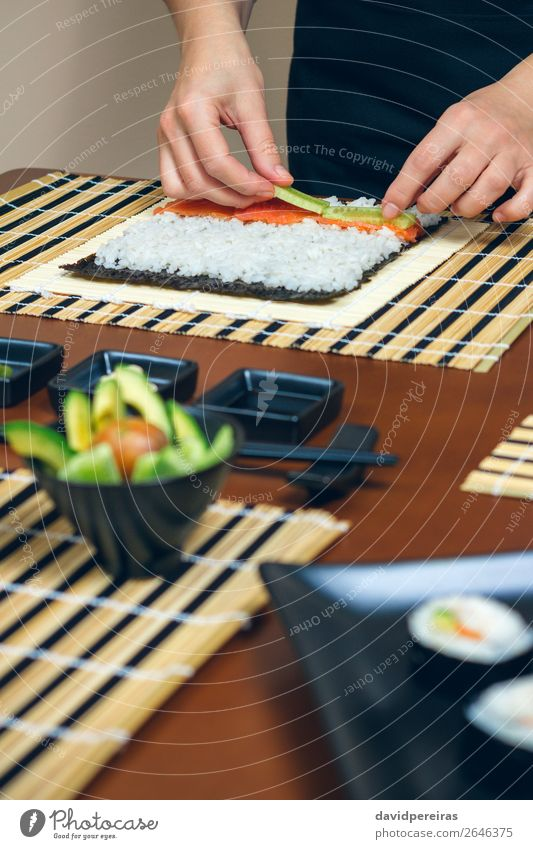 Chef hands placing ingredients on rice Seafood Diet Sushi Bowl Restaurant Human being Woman Adults Hand Make Fresh chef careful cucumber Salmon Rice maki roll