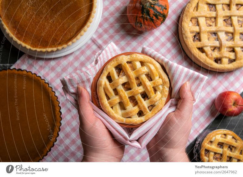 Apple pie held in hands over a table with many pies. Cake Dessert Candy Kitchen Feasts & Celebrations Thanksgiving Christmas & Advent Exceptional Sweet Many