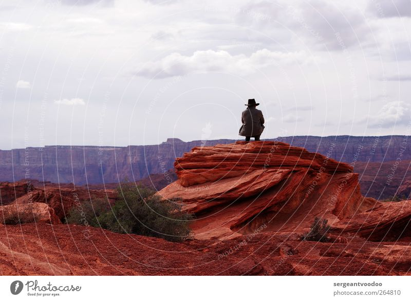 Cowboy on the rocks Man Adults 1 Human being Nature Clouds Horizon Rock Canyon Coat Cowboy hat Observe Relaxation Crouch Dream Cool (slang) Free Infinity Dry