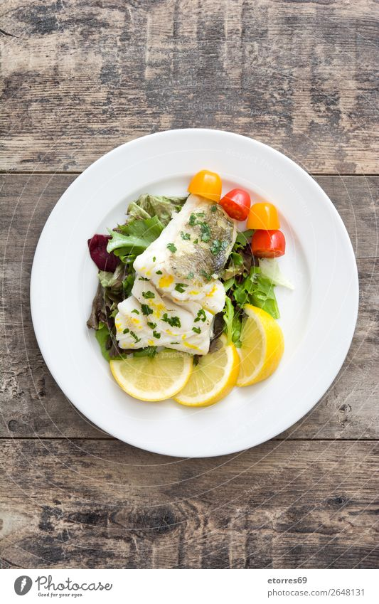 Fried cod fillet and salad in plate on wooden background Cod Fish Frying Salad Food Healthy Eating Food photograph Dish Plate follet Herbs and spices Nutrition