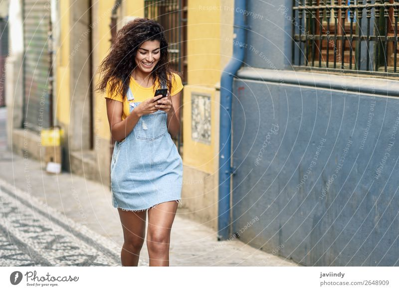 African girl walking on the street looking at her smartphone Lifestyle Style Happy Beautiful Hair and hairstyles Telephone PDA Technology Human being Feminine