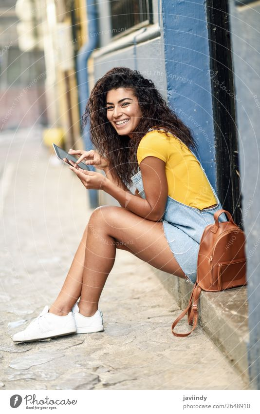 Happy Arab woman sitting on urban step with a digital tablet Woman Human being Youth (Young adults) Young woman Beautiful Joy Black 18 - 30 years Street