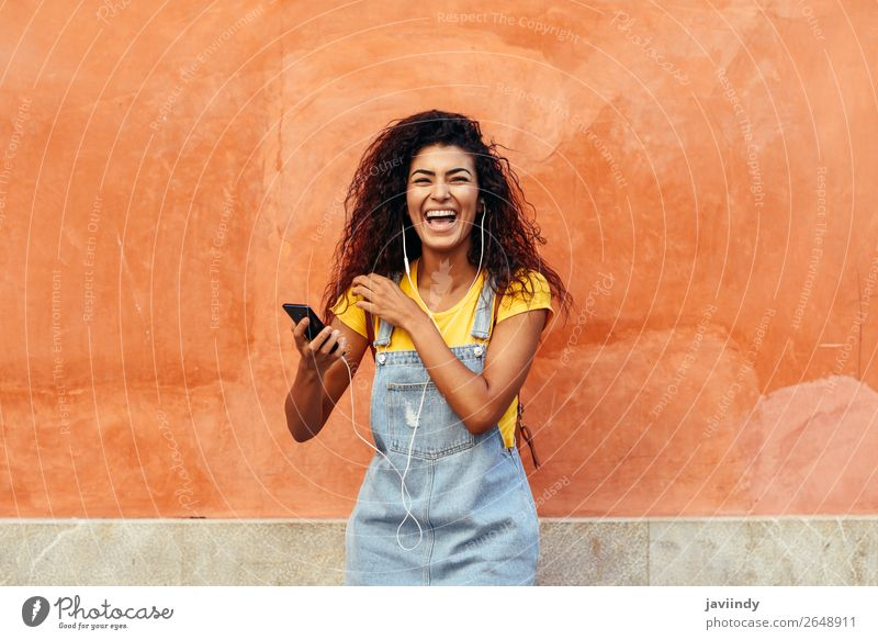 Young Arab woman laughing and listening to music with earphones outdoors Lifestyle Hair and hairstyles Telephone Technology Human being Feminine Young woman