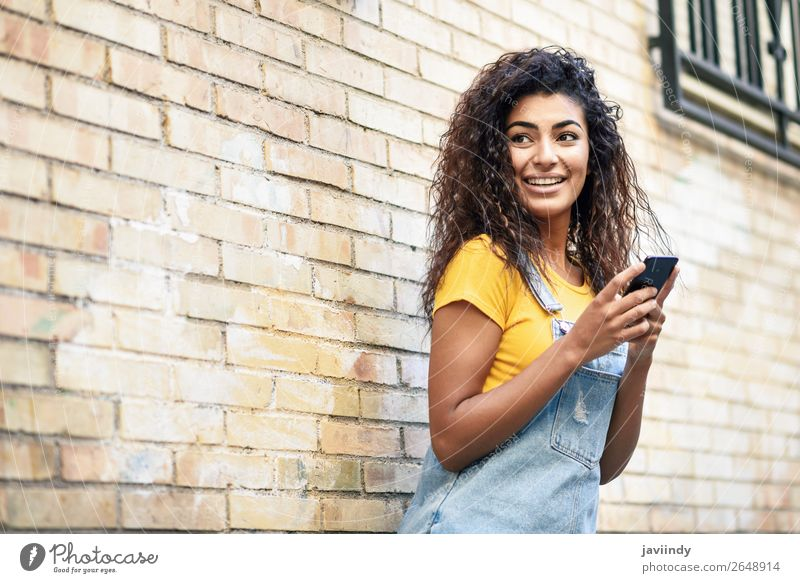 Happy Arab girl using smart phone on brick wall. Lifestyle Style Beautiful Hair and hairstyles Telephone PDA Technology Human being Feminine Young woman