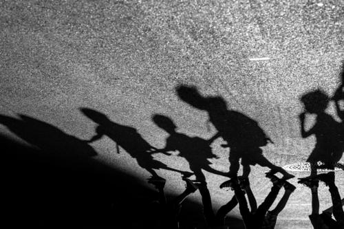 Shadow play - children walk in line across a street Human being Child Girl Boy (child) Body 5 Pedestrian Street Asphalt Walking Town Attachment Going