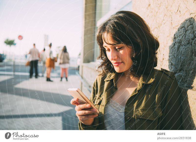 Young woman using her smart phone in the street at sunset Happy Beautiful Leisure and hobbies Telephone Cellphone PDA Technology Woman Adults Autumn Street