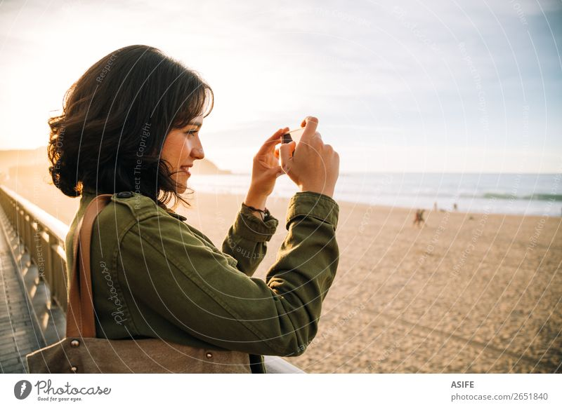 Tourist woman taking pictures with her smart phone Happy Beautiful Leisure and hobbies Vacation & Travel Beach Ocean Telephone Cellphone PDA Technology Woman
