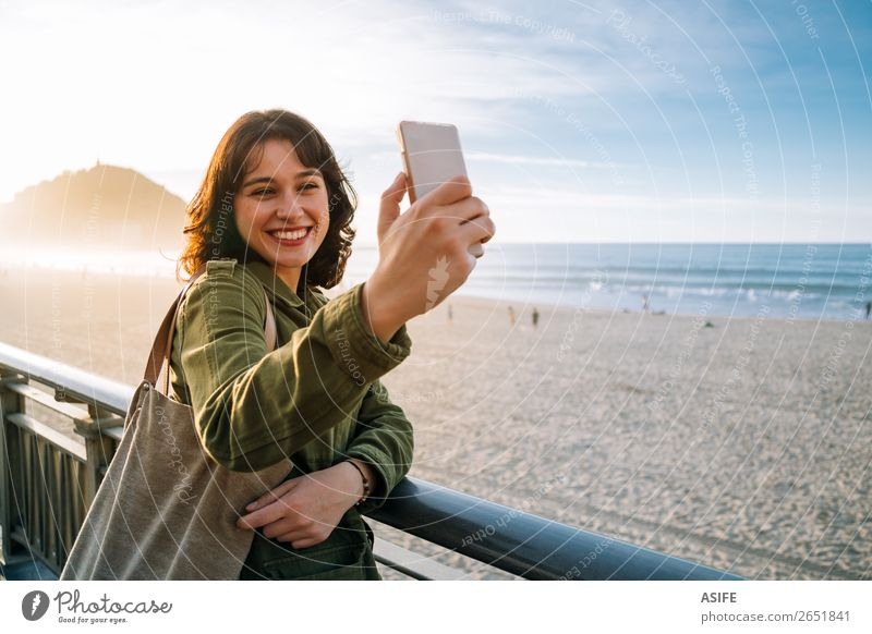 Happy tourist woman taking selfie with her smart phone Beautiful Leisure and hobbies Vacation & Travel Beach Ocean Telephone Cellphone PDA Technology Woman