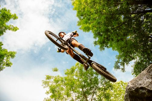 Cyclist extreme jumping from a rock Freedom Summer Mountain Sports Cycling Man Adults Nature Tree Forest Rock Jump Strong Rider bike Extreme bicycle young