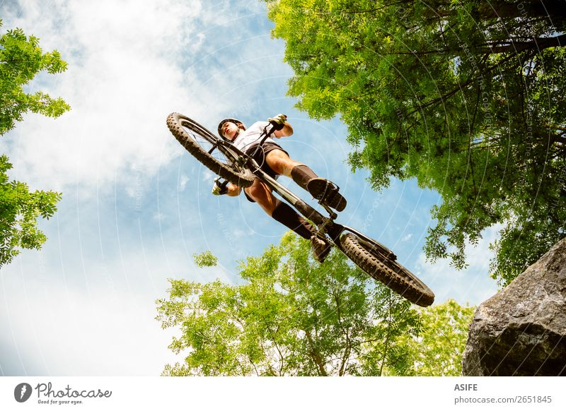 Cyclist extreme jumping from a rock Nature Man Summer Tree Forest Mountain Adults Sports Freedom Rock Jump Action Cycling Strong Balance