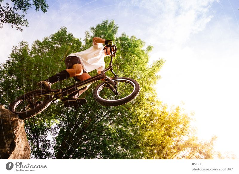 Young cyclist on the edge of a rock ready to jump Nature Man Summer Tree Forest Mountain Adults Sports Freedom Rock Jump Action Cycling Strong Balance