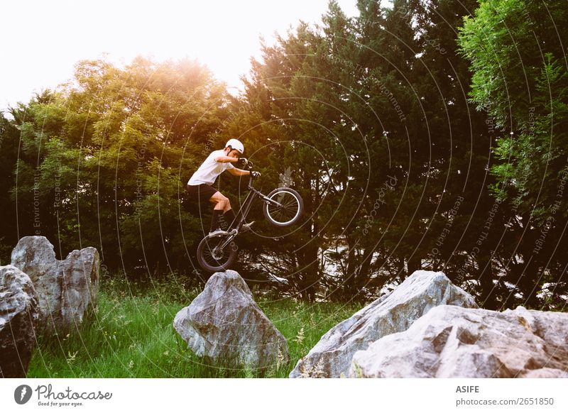 Young trial bycicler making tricks in a rock circuit Nature Man Summer Tree Forest Mountain Adults Sports Freedom Rock Jump Action Cycling Strong Balance