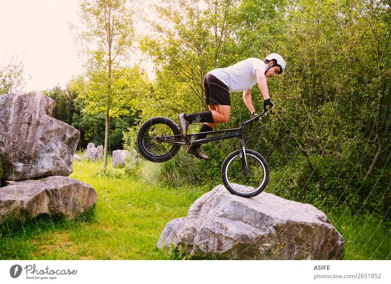 Young trial cyclist making tricks in a rock circuit Nature Man Summer Tree Forest Mountain Adults Sports Freedom Rock Jump Action Cycling Strong Balance