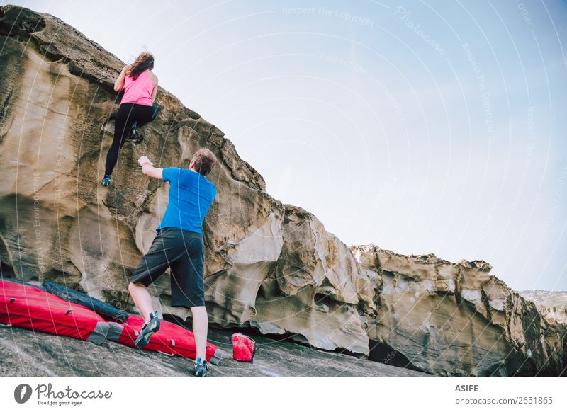 Young couple rock climbing cliffs at the coast helping eachother Joy Leisure and hobbies Adventure Ocean Mountain Hiking Sports Climbing Mountaineering Woman