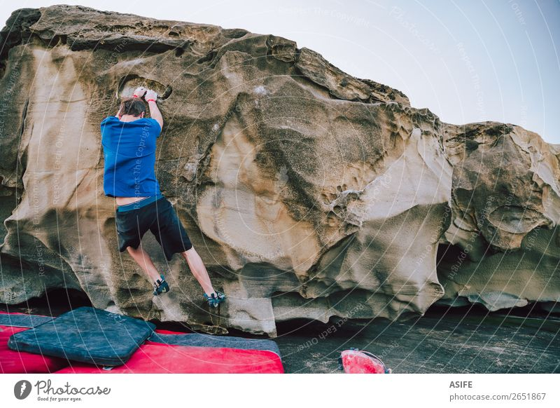 Young rock climber man bouldering Joy Happy Leisure and hobbies Adventure Ocean Mountain Hiking Sports Climbing Mountaineering Man Adults Nature Rock Coast