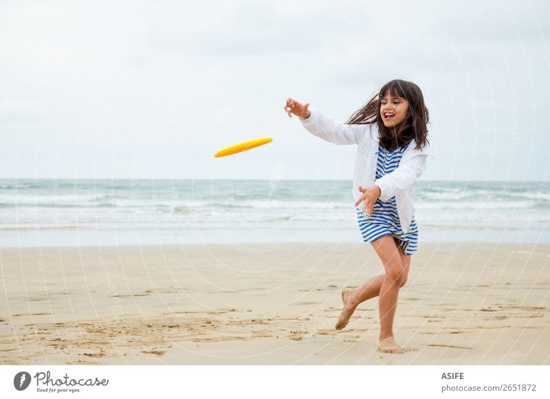Gril playing frisbee Joy Happy Beautiful Leisure and hobbies Playing Beach Waves Sports Child Sand Clouds Coast Dress Cute Blue Yellow Kid Frisbee action girl